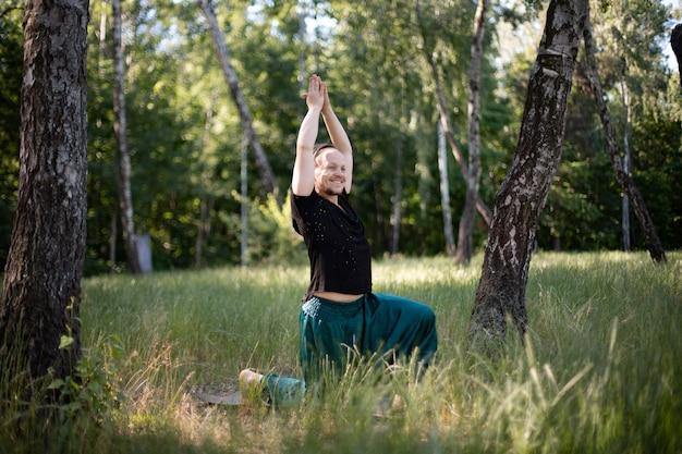 Man staat in een asana yoga te doen in het park op groen gras. internationale dag van yoga