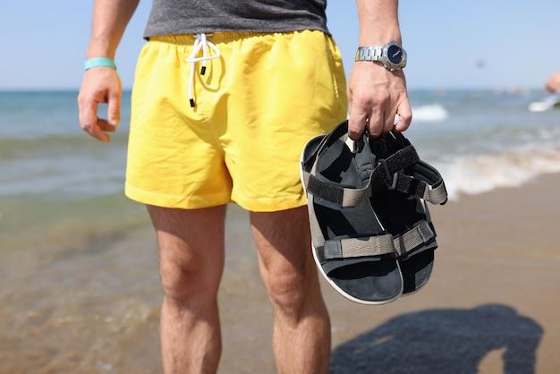 Man staat in een t-shirt en korte broek in zijn handen met zijn schoenen tegen de achtergrond van de zee