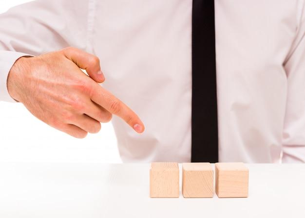 Man staat in een wit shirt en wijst met een vinger naar de kubus.