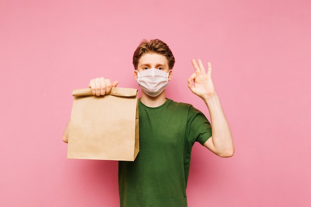 Man staat met een pakje eten uit de bevalling in zijn handen op een medisch masker op zijn gezicht, kijkt naar de camera en toont een gebaar ok. coronapandemie. quarantaine. covid19.