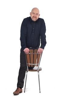 Man staat met een stoel op een witte achtergrond, knieën over de stoel