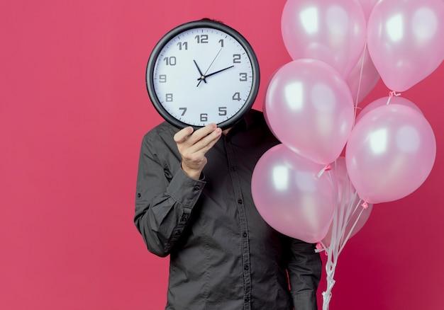 Man staat met helium ballonnen bedrijf en sluitend gezicht geïsoleerd op roze muur
