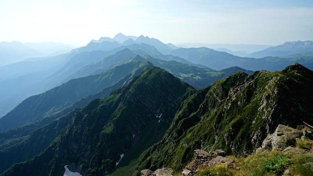 Man staat met russische vlag op de top van de berg black pillar, krasnaya polyana, sochi, rusland