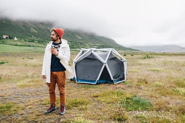 Man staat naast moderne tent in ijsland