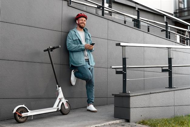 Man staat naast zijn scooter terwijl hij op zijn telefoon kijkt