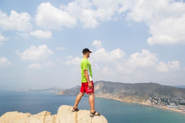 Man staat op de top van een berg en kijkt naar de zee