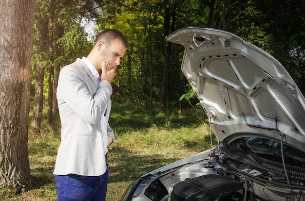 Man staat op de weg bij de kapotte auto en denkt hoe het te repareren