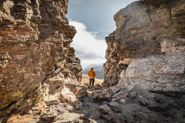 Man staat op een top tussen rotsen in het rocky mountain national park en kijkt uit over de bergketen op een koude en winderige dag