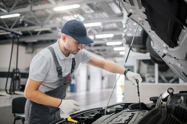 Man staat op geopende lichaam van auto en werkt. hij is serieus en geconcentreerd. hij houdt een zwarte sleutel in de rechterhand. man werkt in handschoenen.