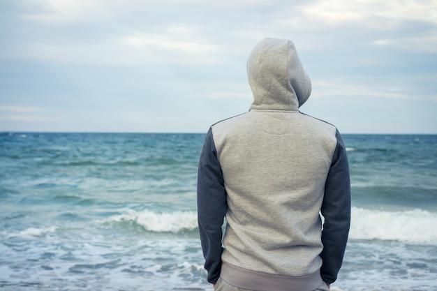Man staat op het strand in een trainingspak met een capuchon en kijkt naar de zee