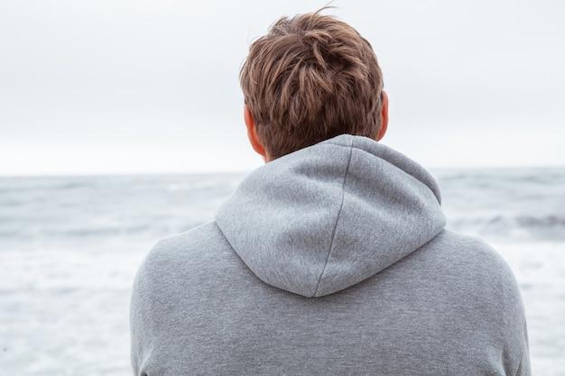 Man staat terug naar de camera aan de oceaankust en bewondert de natuur