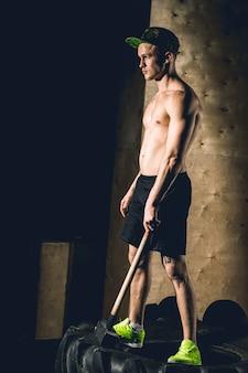 Man staat wielband met hammer sledge crossfit training