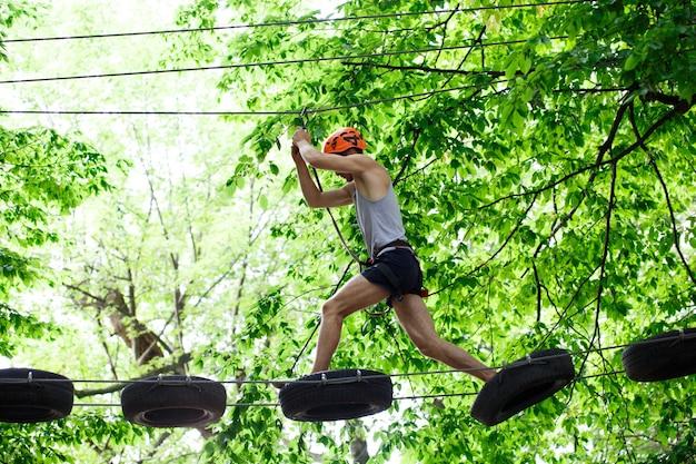 Man stappen op de houten planken die in de lucht hangen
