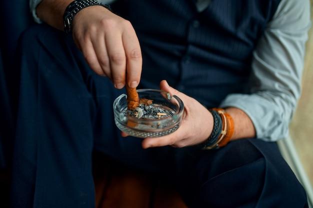 Man steekt een sigaar uit in een asbak, close-up weergave