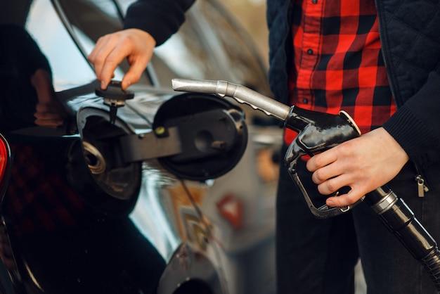 Man steekt het pistool in de autotank op benzinestation