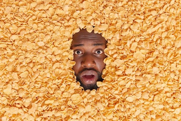Man steekt hoofd in cornflakes eet ontbijtgranen als ontbijt reageert verrassend op iets ongelooflijks houdt gezonde voeding in