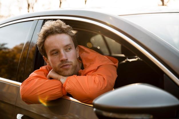 Man steekt zijn hoofd uit het autoraam tijdens een roadtrip