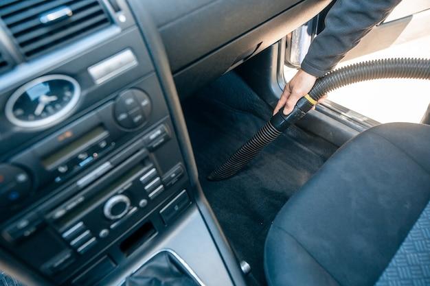 Man stofzuigen, stofzuigen van een auto-interieur door stofzuiger, reinigingsconcept