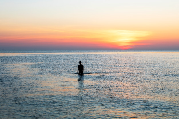 Man stond bij de zee en keek naar de zon opkomen in de ochtend. hij zag er gelukkig en warm uit