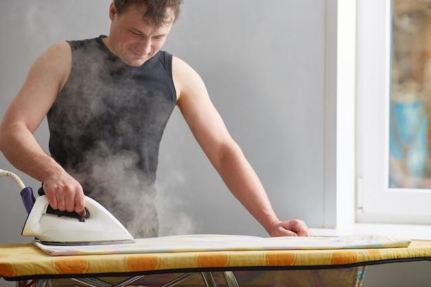 Man strijken van wasgoed met een stoomgenerator. stoom rond. het concept van het zorgen voor het huis, het helpen van mannen in huishoudelijke taken.