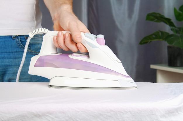 Man strijkt linnen met een zwart strijkijzer op een strijkplank.