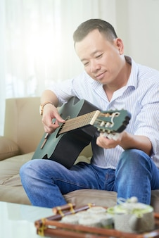 Man studeert om gitaar te spelen