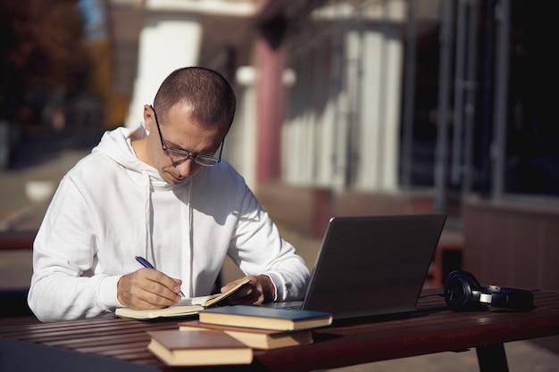 Man studeert op laptop en schrijft in een notitieblok zittend op straat aan een tafel. sociale afstand nemen tijdens het coronavirus