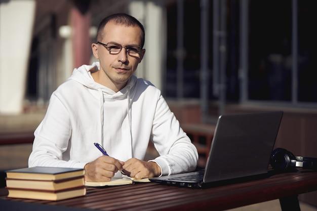 Man studeert op laptop en schrijft in een notitieblok zittend op straat aan een tafel