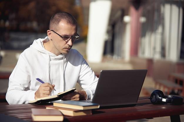 Man studeert op laptop en schrijft in notitieblok zittend op straat aan tafel. sociale afstand nemen tijdens het coronavirus