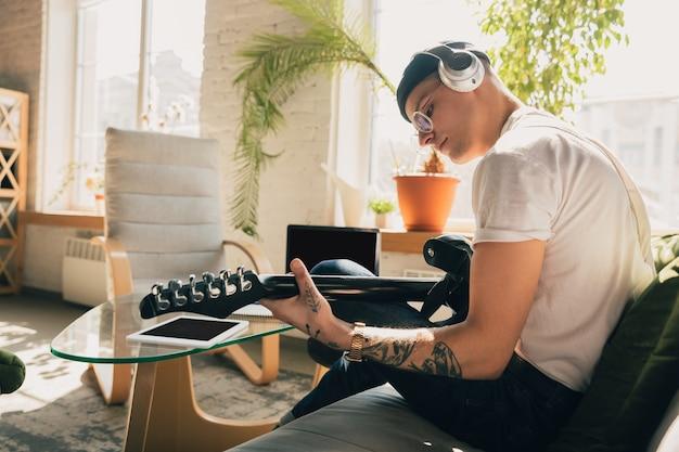 Man studeert thuis tijdens online cursussen of gratis informatie door hemzelf. wordt muzikant, gitarist terwijl hij geïsoleerd is, in quarantaine tegen verspreiding van het coronavirus. met behulp van laptop, smartphone, koptelefoon.