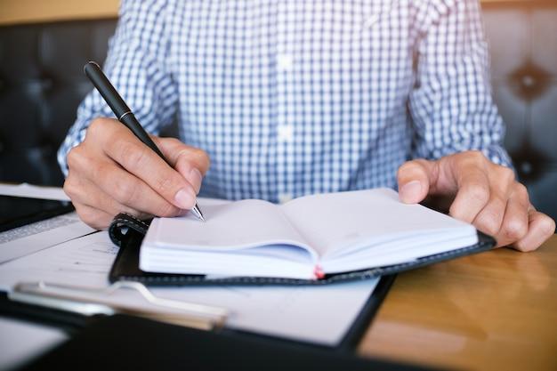 Man student schrijft informatie uit draagbare tablet terwijl hij zich voorbereidt op lezingen in de universitaire campus
