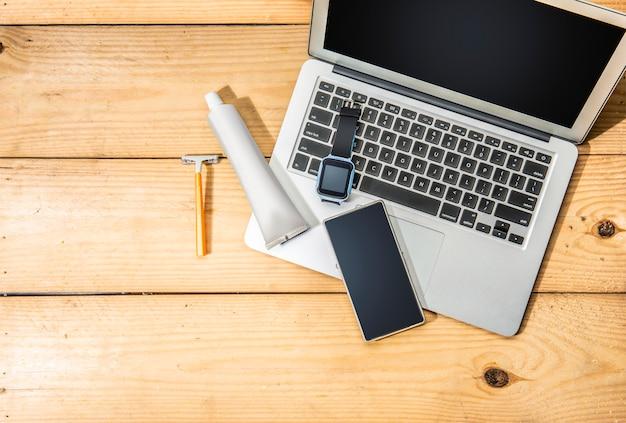 Man-stuffs zoals laptop, smartwatch, mobiele telefoon, geel scheerapparaat en tandpastaproducten voor op reis