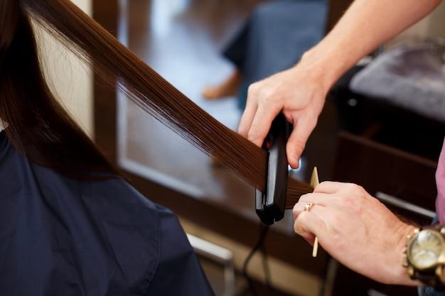Man stylist lijnt het haar van de klant uit met een straightener