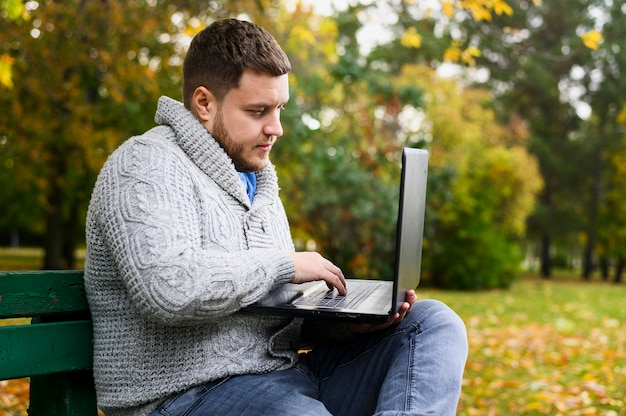Man surfen op laptop zittend op een bankje