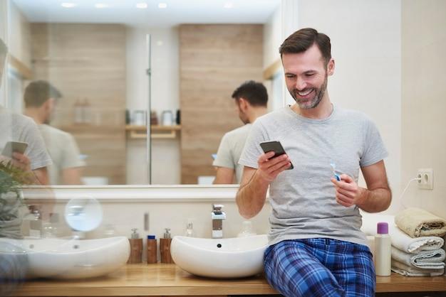 Man tanden poetsen en mobiele telefoon gebruiken in de badkamer