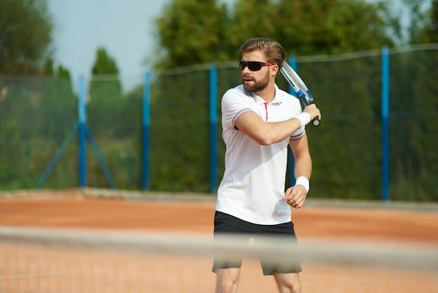 Man tennissen op zonnige dag
