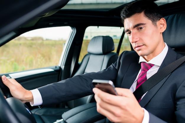 Man texting tijdens het rijden met de auto