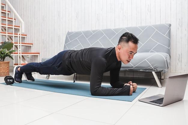 Man thuis doet oefeningen en strekt zich uit om zich op te warmen terwijl hij naar een online video-fitnessles kijkt