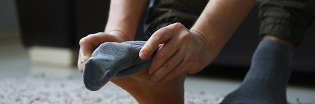 Man thuis in de ochtend zet grijze sokken op zijn been