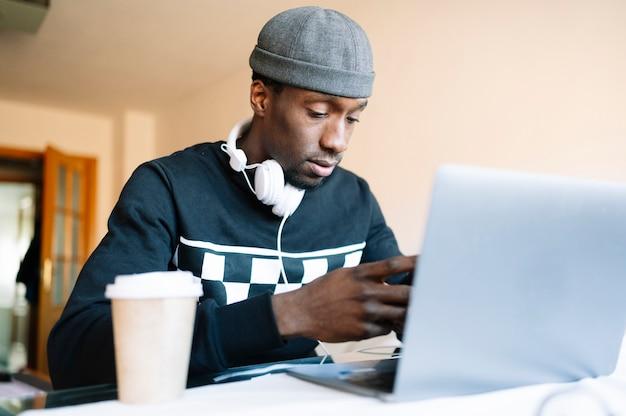 Man thuis met smartphone en laptop