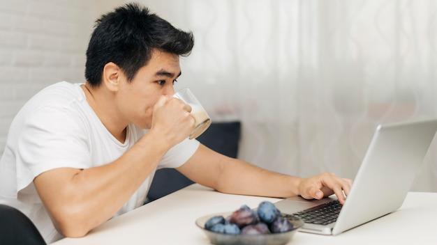 Man thuis tijdens de pandemie met behulp van laptop en koffie drinken