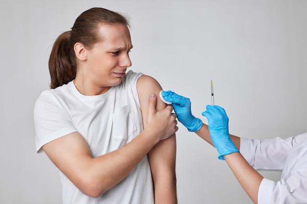 Man tijdens coronavirusvaccinatie, covid-19-immunisatie. arts die vaccininjectie geeft aan mannelijke patiënt