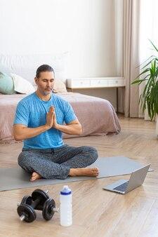 Man tijdens online stomen. meditatiebeoefening - gebedshouding. verticale foto.