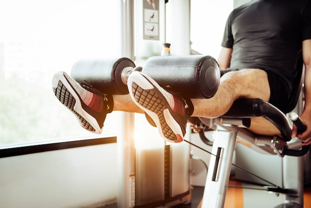 Man tillen gewicht door twee benen voor het uitrekken van spieren op fitness gym in prive-condominium