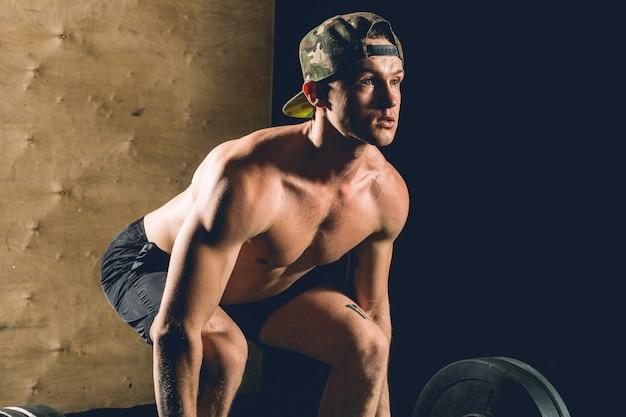 Man tillen gewichten. gespierde man training in de sportschool doen oefeningen met barbell