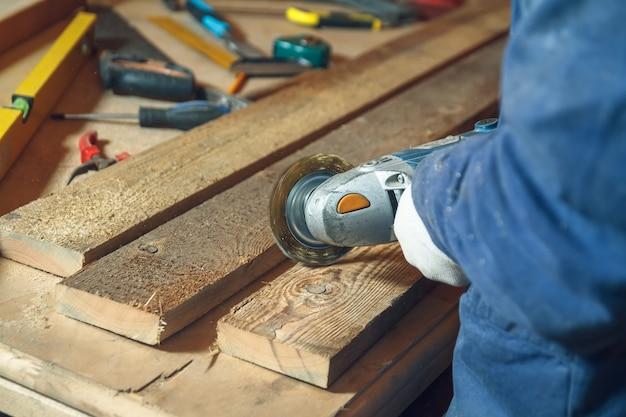 Man timmerman freest het stuk hout door een slijpmachine in zijn eigen werkplaats