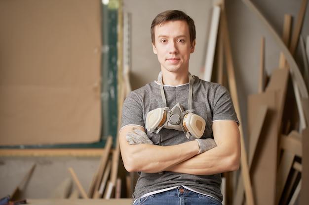 Man timmerman met gekruiste armen in werkplaats