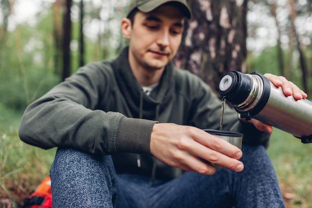 Man toerist giet hete thee uit thermos in lente bos kamperen, reizen