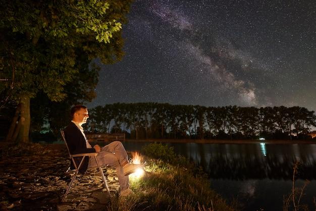 Man toerist met een rust op de oever van het meer in de buurt van kampvuur, zittend op een stoel onder grote boom, genieten van prachtig uitzicht op de nachtelijke hemel vol met sterren en melkweg, stadslichten op de achtergrond.