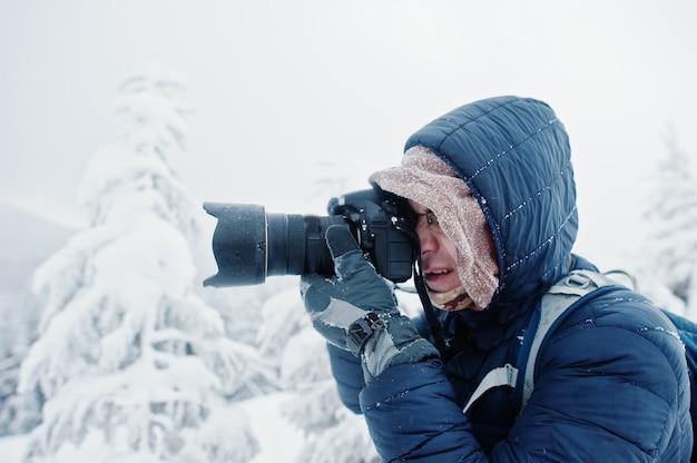 Man toeristische fotograaf met rugzak, op berg met pijnbomen bedekt met sneeuw